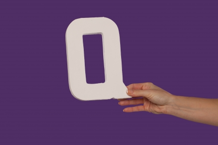 Female hand holding up the uppercase capital letter Q isolated against a purple background conceptual of the alphabet, writing, literature and typeface Stock Photo - 16132765
