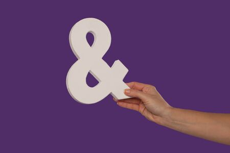Female hand holding up a white ampersand symbol isolated against a purple background signifying plus, and, in conjunction with, or jointly Stock Photo - 16132767
