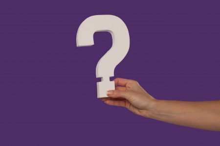 Female hand holding up a white question mark against a purple background conceptual of questions, query, why or what. Stock Photo - 16132752