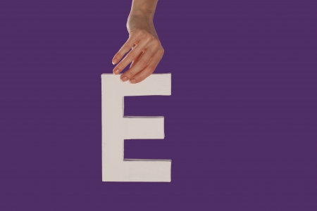 majuscule: Female hand holding up the uppercase capital letter E isolated against a purple background conceptual of the alphabet, writing, literature and typeface