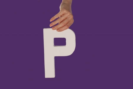 majuscule: Female hand holding up the uppercase capital letter P isolated against a purple background conceptual of the alphabet, writing, literature and typeface Stock Photo