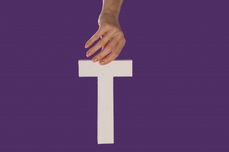 majuscule: Female hand holding up the uppercase capital letter T isolated against a purple background conceptual of the alphabet, writing, literature and typeface