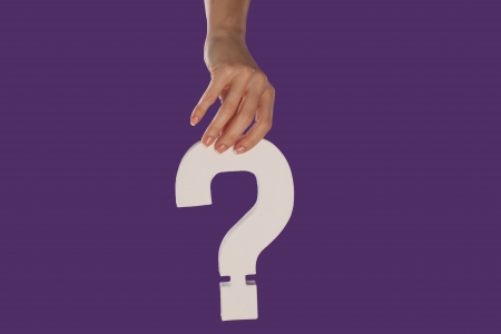 Female hand holding up a white question mark against a purple background conceptual of questions, query, why or what. Stock Photo - 16132712