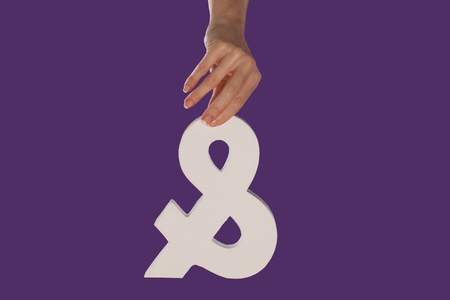 conjunction: Female hand holding up a white ampersand symbol isolated against a purple background signifying plus, and, in conjunction with, or jointly Stock Photo