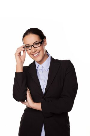 entrepeneur: Smiling successful confident businesswoman, manageress or entrepeneur standing with her hand to her glasses isolated on white