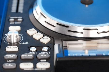 Closeup detail of a DJ turntable and control knobs on the deck for mixing music at a disco or nightclub photo