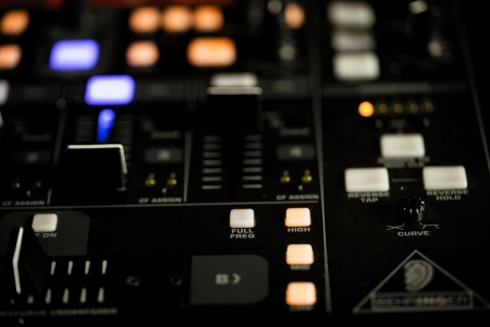 recorded: Illuminated lights on the console of a DJ deck at night for mixing and fading recorded music in a disco or nightclub