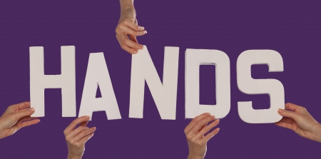 extremity: White alphabet lettering spelling HANDS held up over a purple studio background by outstreched female hands Stock Photo