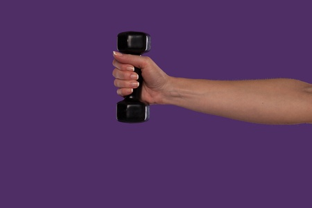 hand grip: Female hand holding a black dumbbell with the arm extended straight out over a purple studio background