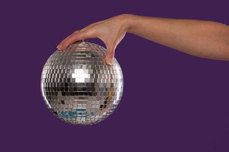Female hand holding a suspended shiny silver mirrored disco ball over a purple studio background photo