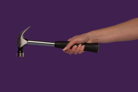 Female hand holding a steel claw hammer over a purple studio background in a DIY, home maintenance and construction concept photo