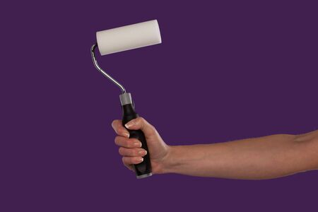 Female hand holding a paint roller over a purple studio background in a DIY and home redecorating concept photo