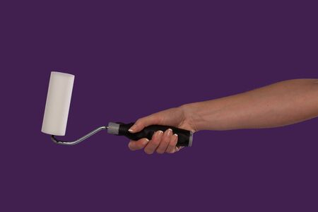 Hand of a female decorator holding a paint roller over a purple studio background in a DIY, renovation and home redecorating concept photo