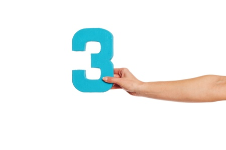 quantity: Female hand holding up the number 3 against a white background conceptual of numbers, measurement, amount, quantity, accounting and mathematics Stock Photo