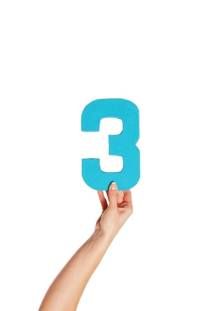 aloft: Female hand holding up the number 3 against a white background conceptual of numbers, measurement, amount, quantity, accounting and mathematics Stock Photo