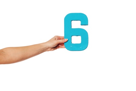 number six: Female hand holding up the number 6 against a white background conceptual of numbers, measurement, amount, quantity, accounting and mathematics Stock Photo