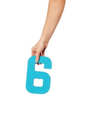 number 6: Female hand holding up the number 6 against a white background conceptual of numbers, measurement, amount, quantity, accounting and mathematics Stock Photo