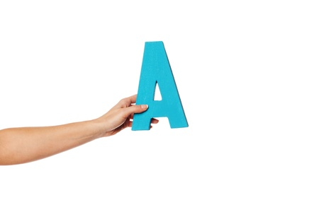 majuscule: Female hand holding up the uppercase capital letter A isolated against a white background conceptual of the alphabet, writing, literature and typeface Stock Photo