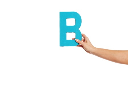 majuscule: Female hand holding up the uppercase capital letter B isolated against a white background conceptual of the alphabet, writing, literature and typeface Stock Photo