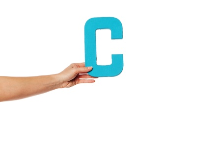 majuscule: Female hand holding up the uppercase capital letter C isolated against a white background conceptual of the alphabet, writing, literature and typeface Stock Photo