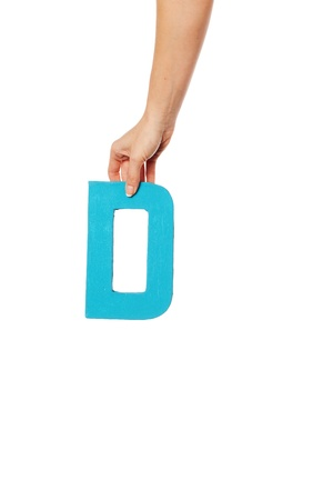 majuscule: Female hand holding up the uppercase capital letter D isolated against a white background conceptual of the alphabet, writing, literature and typeface