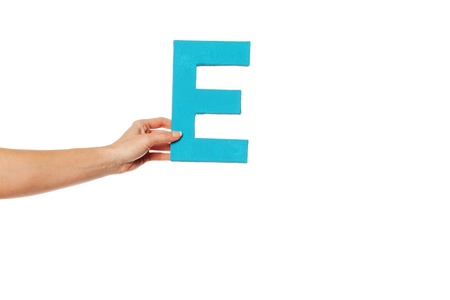 majuscule: Female hand holding up the uppercase capital letter E isolated against a white background conceptual of the alphabet, writing, literature and typeface