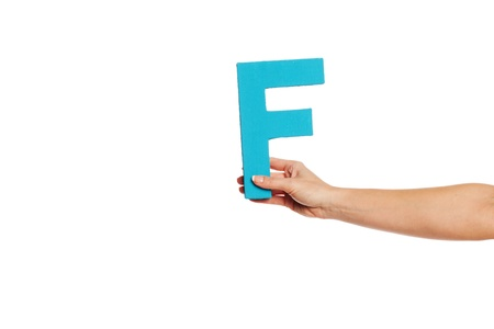 majuscule: Female hand holding up the uppercase capital letter F isolated against a white background conceptual of the alphabet, writing, literature and typeface