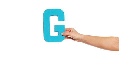 majuscule: Female hand holding up the uppercase capital letter G isolated against a white background conceptual of the alphabet, writing, literature and typeface Stock Photo