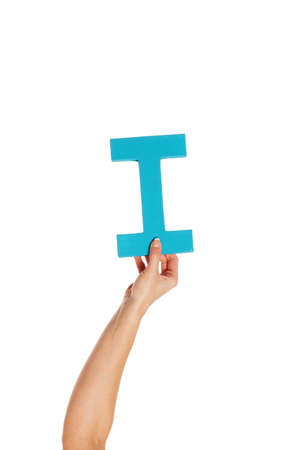 aloft: Female hand holding up the uppercase capital letter I isolated against a white background conceptual of the alphabet, writing, literature and typeface