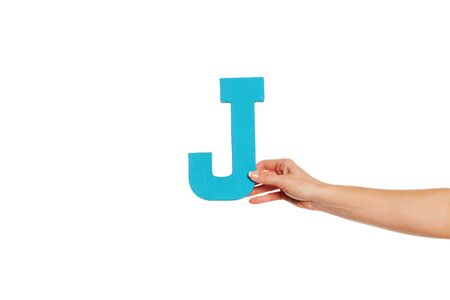 Female hand holding up the uppercase capital letter J isolated against a white background conceptual of the alphabet, writing, literature and typeface