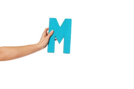 majuscule: Female hand holding up the uppercase capital letter M isolated against a white background conceptual of the alphabet, writing, literature and typeface