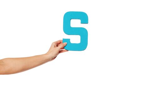 majuscule: Female hand holding up the uppercase capital letter S isolated against a white background conceptual of the alphabet, writing, literature and typeface