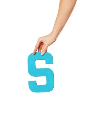 aloft: Female hand holding up the uppercase capital letter S isolated against a white background conceptual of the alphabet, writing, literature and typeface