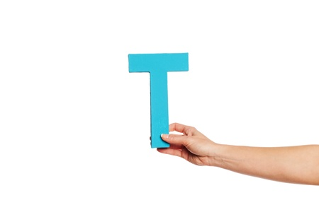 majuscule: Female hand holding up the uppercase capital letter T isolated against a white background conceptual of the alphabet, writing, literature and typeface