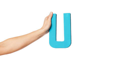 aloft: Female hand holding up the uppercase capital letter U isolated against a white background conceptual of the alphabet, writing, literature and typeface Stock Photo