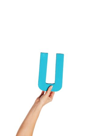 majuscule: Female hand holding up the uppercase capital letter U isolated against a white background conceptual of the alphabet, writing, literature and typeface Stock Photo