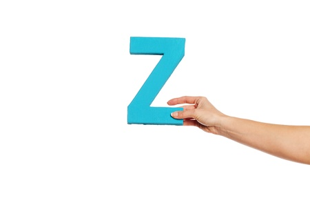 majuscule: Female hand holding up the uppercase capital letter Z isolated against a white background conceptual of the alphabet, writing, literature and typeface Stock Photo