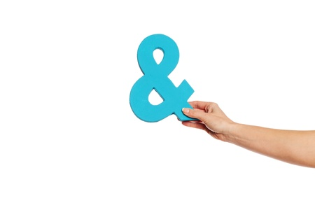 Female hand holding up a blue ampersand symbol isolated against a white background signifying plus, and, in conjunction with, or jointly Stock Photo - 16147435