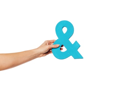aloft: Female hand holding up a blue ampersand symbol isolated against a white background signifying plus, and, in conjunction with, or jointly