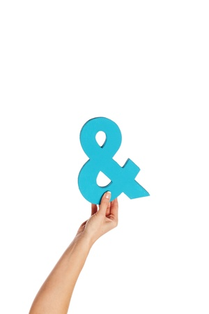 Female hand holding up a blue ampersand symbol isolated against a white background signifying plus, and, in conjunction with, or jointly