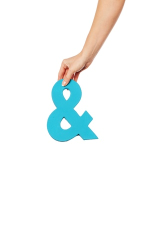 conjunction: Female hand holding up a blue ampersand symbol isolated against a white background signifying plus, and, in conjunction with, or jointly