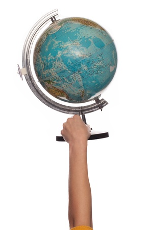 Female hand holding up a globe showing the continents and oceans isolated on a white studio background photo