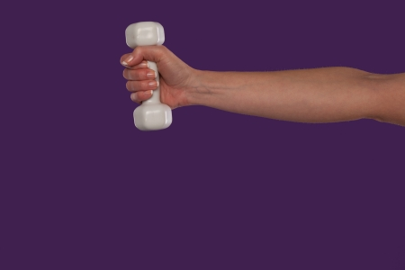 arm extended: Female hand holding a small white dumbbell with the arm extended straight out over a purple studio background