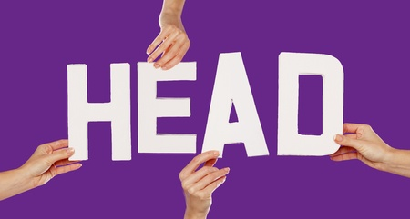 literary: Female hands holding the text word for HEAD in white capital letters isolated on a purple studio background