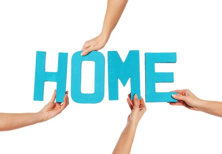 hands holding house: Female hands holding text word for HOME in turquoise blue capital letters isolated on a white studio background