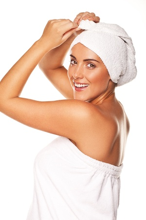 therapeutical: Beautiful woman tying up her wet hair in a towel after bathing in a fresh clean conceptual image for health and beauty isolated on white Stock Photo