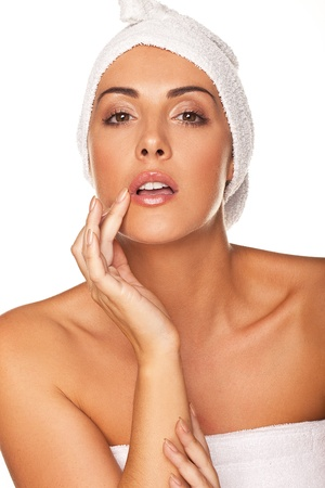 therapeutical: Beautiful graceful woman with her head wrapped in a towel applying lip gloss with the tip of her finger isolated on white Stock Photo