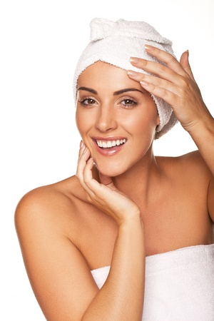 rejuvenated: Vivacious beautiful woman wrapped in a white towel smiling and laughing as she feels rejuvenated after a spa treatment isolated on white