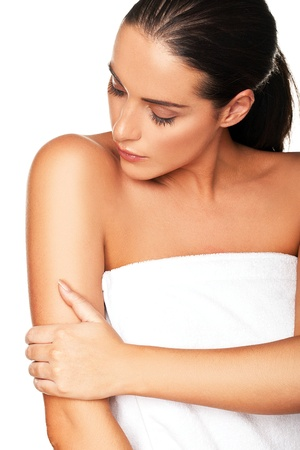 therapeutical: Beautiful young woman wrapped in a white towel caressing her bare arm and looking down isolated on white Stock Photo