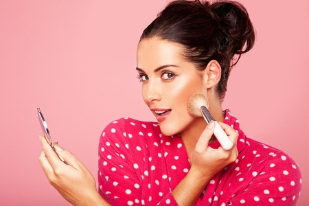 therapeutical: Beautiful young brunette woman applying blusher to her cheek using a cosmetic brush and small compact mirror